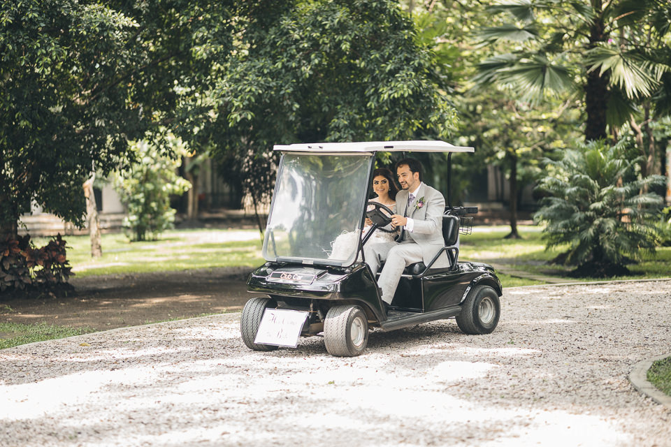 newlywed bride and groom arrive to wedding reception in a golf c