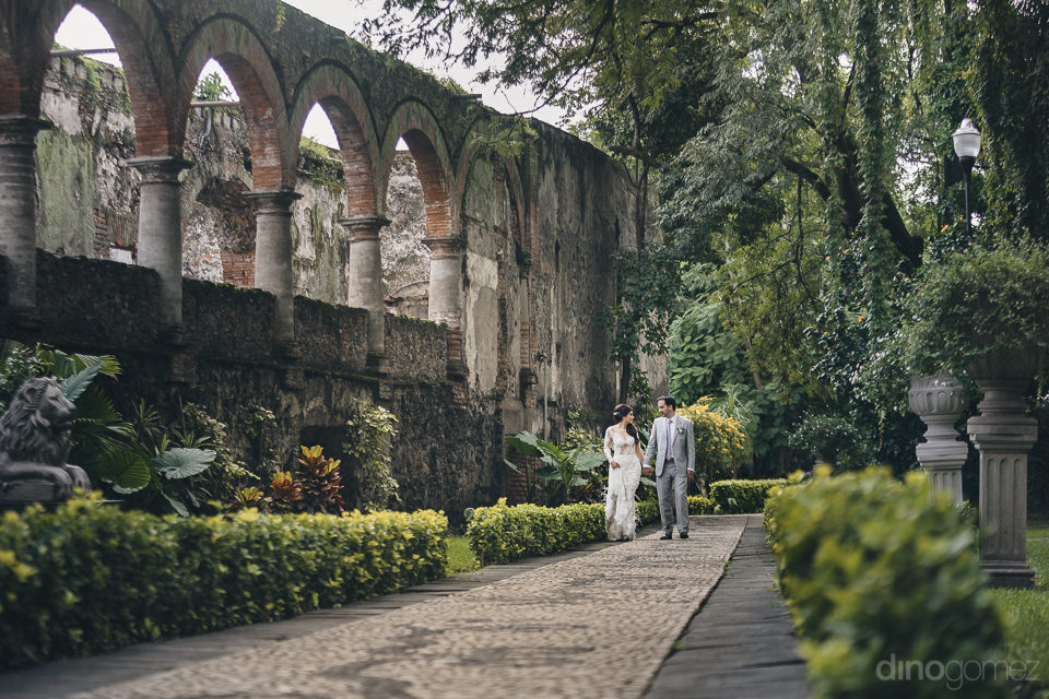 newlyweds walk through green lush gardens of a historic mexican