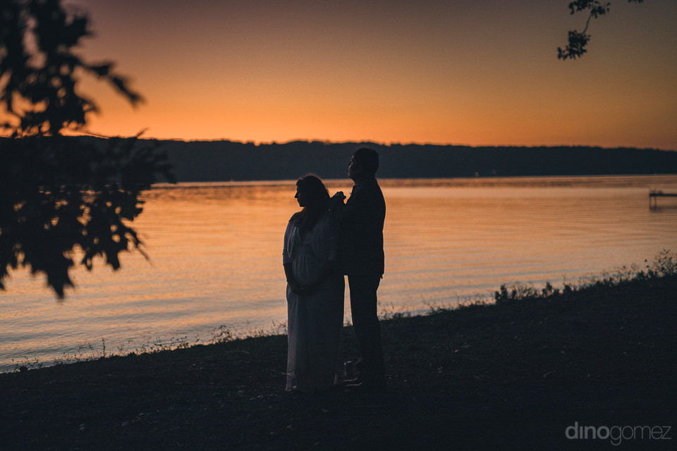 newlyweds watch sunset by lake in artistic wedding photo by dino