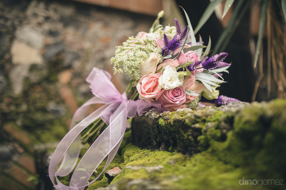 beautiful bridal bouquet with pink roses sits on green moss cove