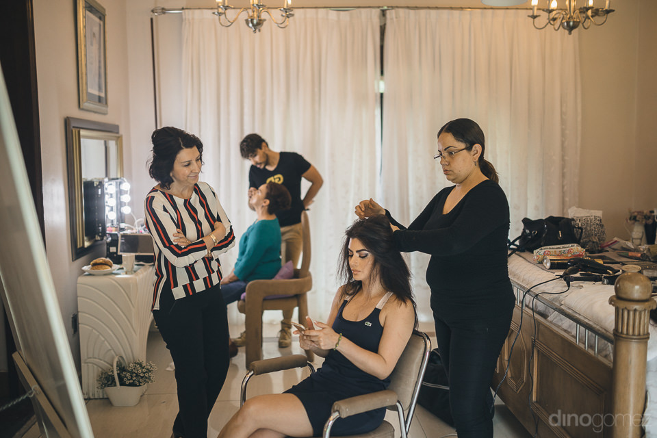 hair and makeup artists prepare for the bride for her wedding in