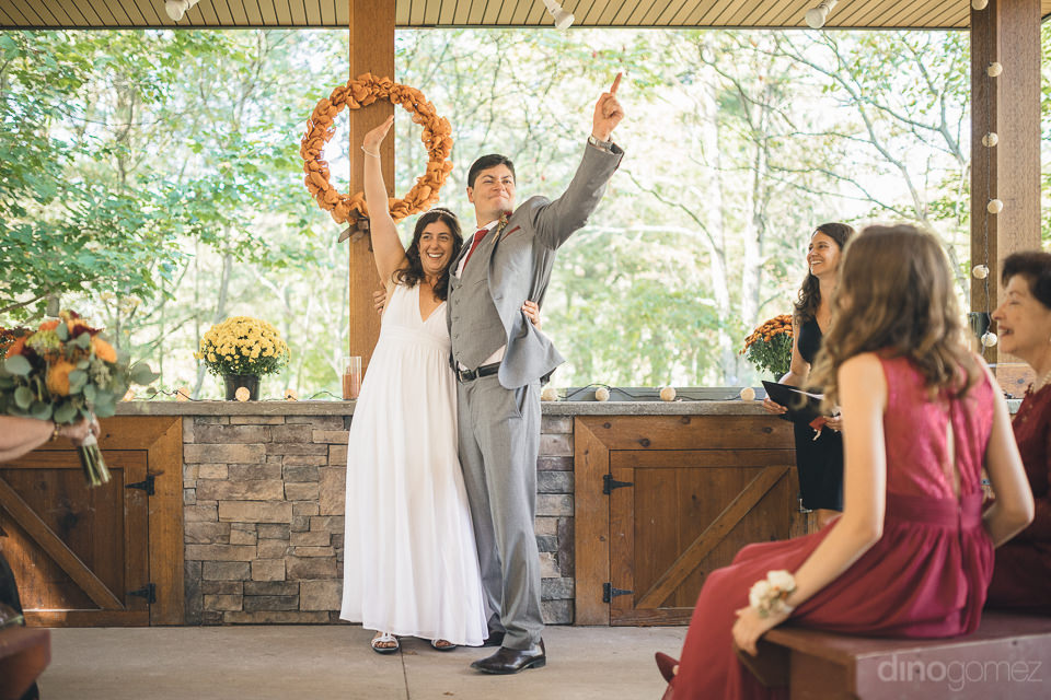 happy newlyweds raise their hands in cele