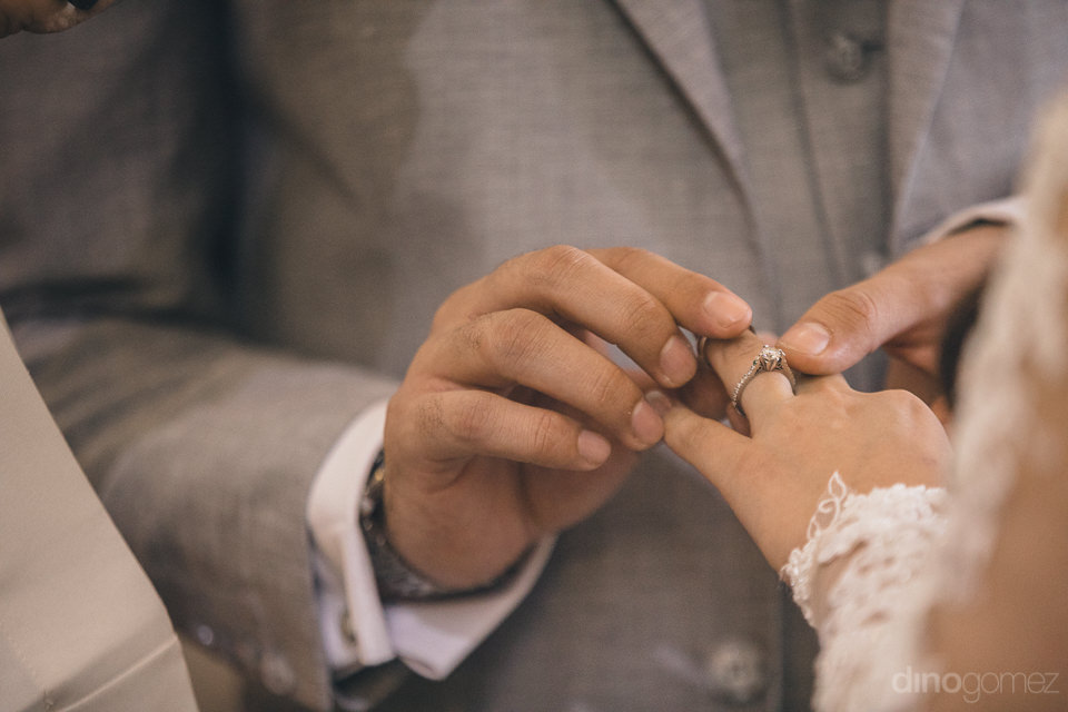 groom puts ring on brides finger in wedding photo by mexico wedd