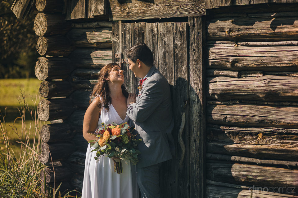 newlyweds stand next to old log cabin in wedding photo by new yo