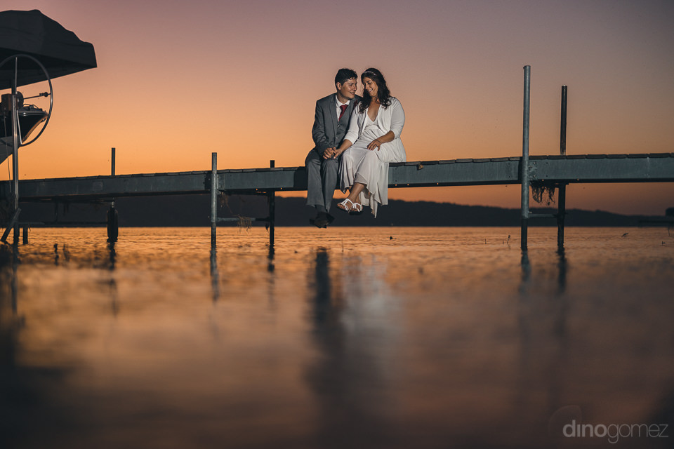 newlyweds sit on dock of lake at sunset artistic romantic weddin