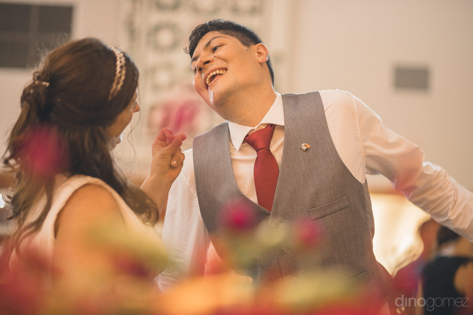 smiling newlyweds laugh and enjoy their wedding reception photo