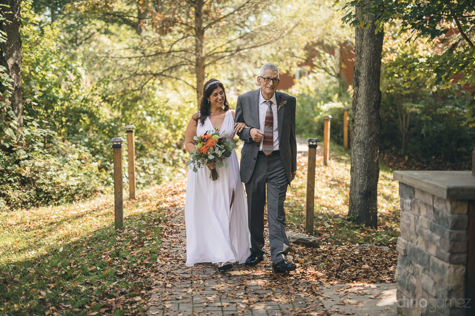 bride walking down aisle with father in outdoor nature summer we