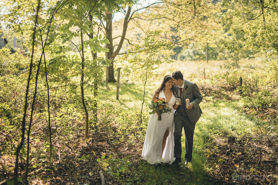 newlyweds walk through sunny countryside in new york state