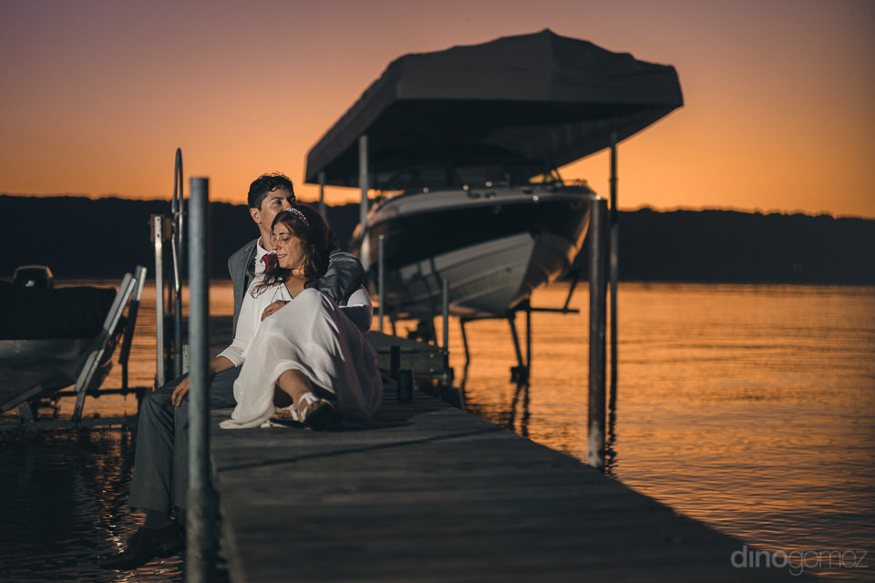 bride and groom sitting on wooden dock at sunset by lake in new