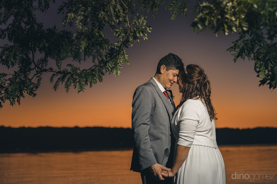 newlyweds by lake at sunset in romantic photo by dino gomez