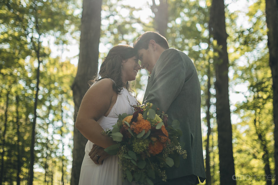 sun shines through trees down on newlyweds in forest