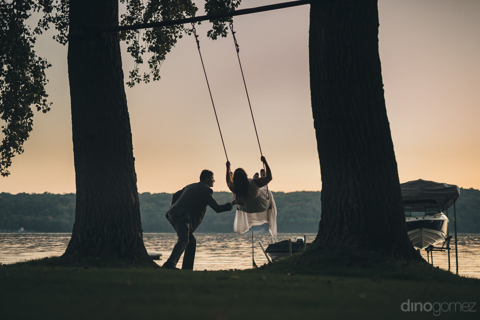bride being pushed on swing by groom at sunset by lake in artist