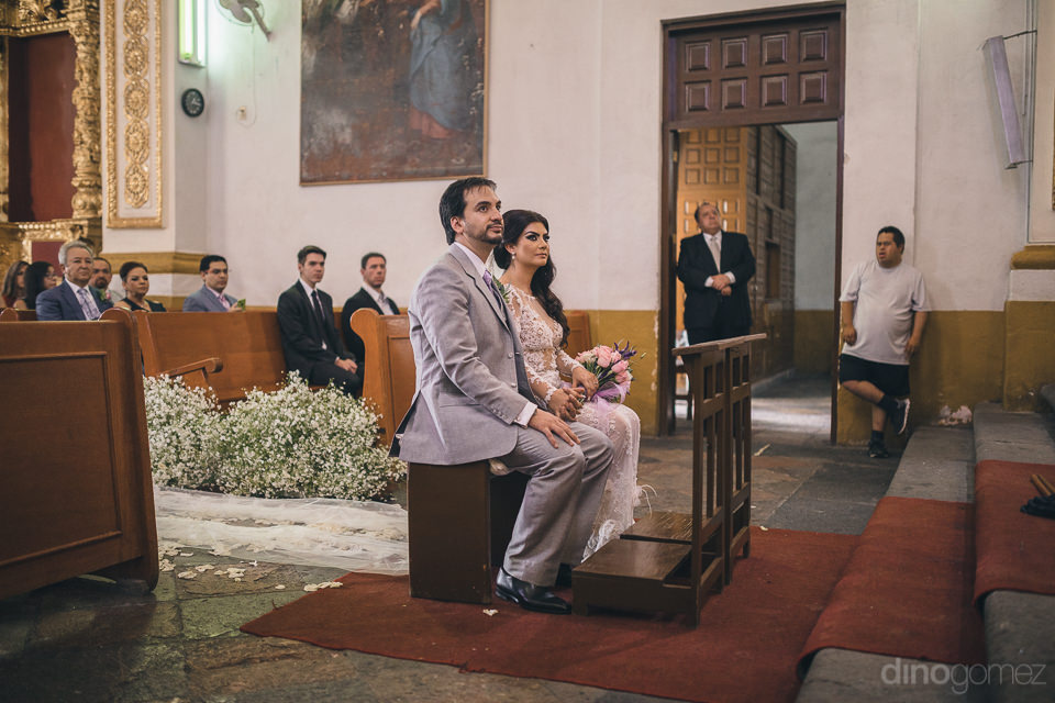bride and groom sit at wedding altar during ceremony