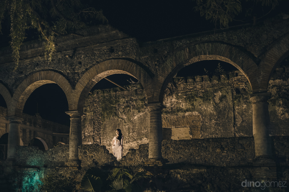 bride alone at night standing next to stone pillars in artistic