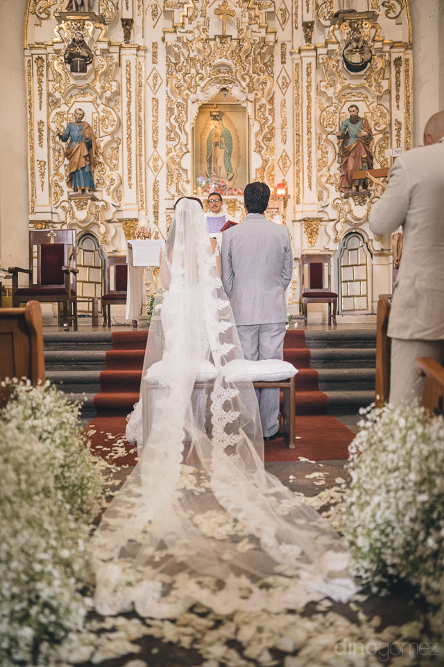 bride and groom stand together at wedding altar inside mexican c