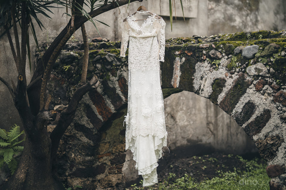 luxury white wedding dress hangs from a tree in the courtyard of