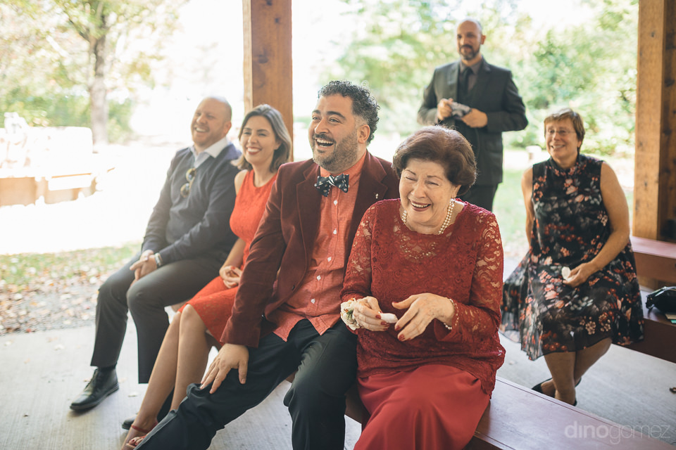 wedding guests laugh and enjoy wedding ceremony photographed by