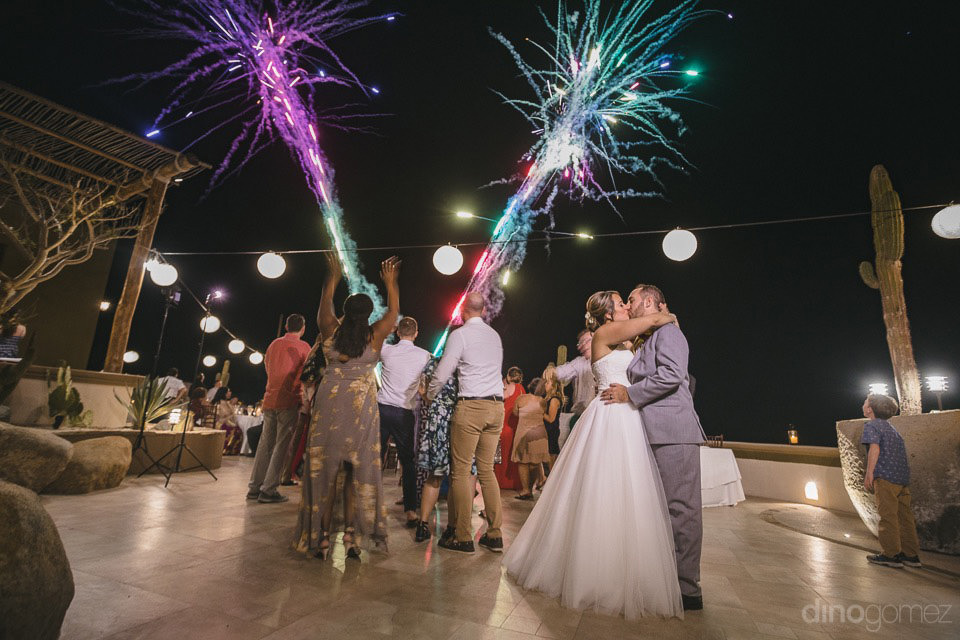 couple kissing with fireworks in the back - Jo & KC's Wedding in Cabo