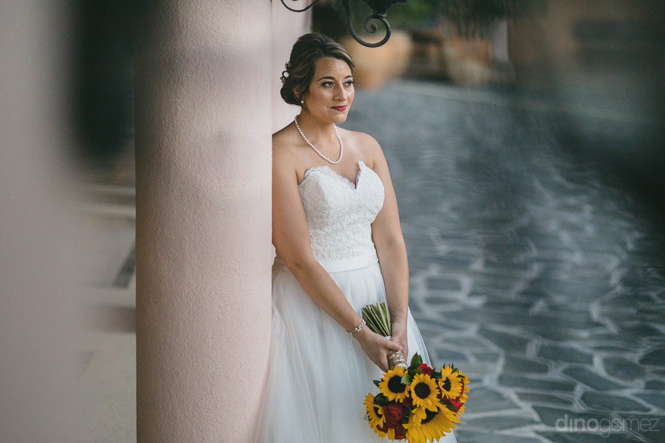 Bride leaning on a column  - Jo & KC's Wedding in Cabo