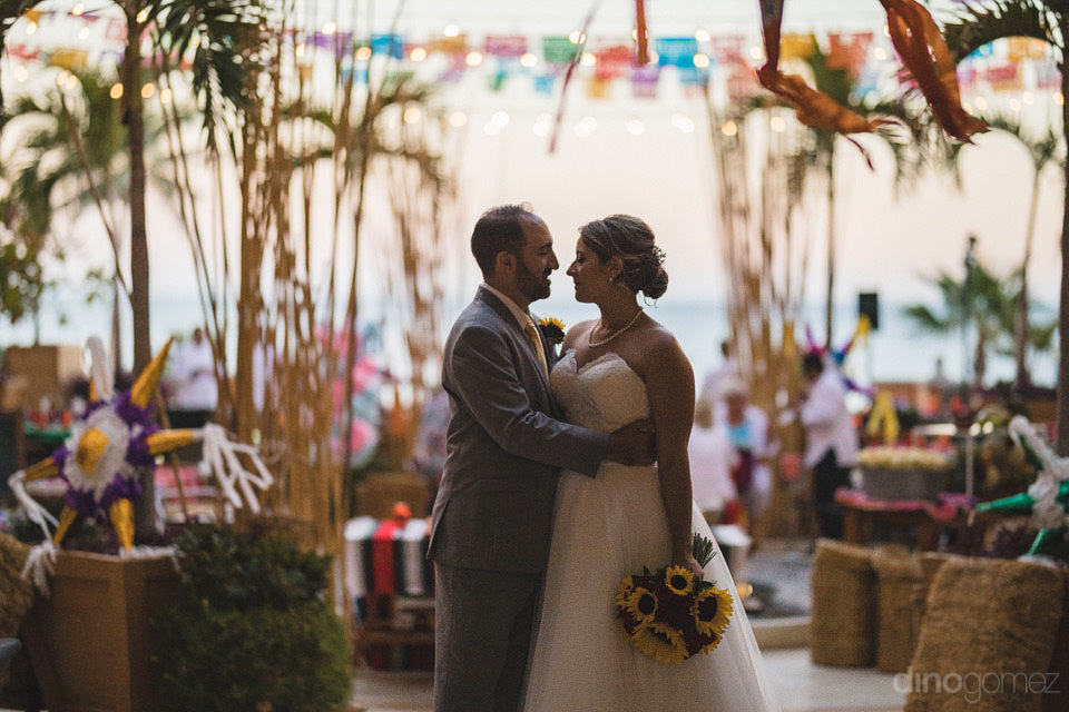 couple with a festive mexican decor behind them - Jo & KC's Wedding in Cabo