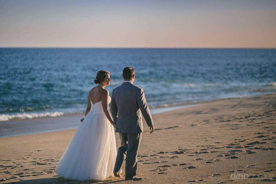 couple walking on the beach at sunset - Jo & KC's Wedding in Cabo