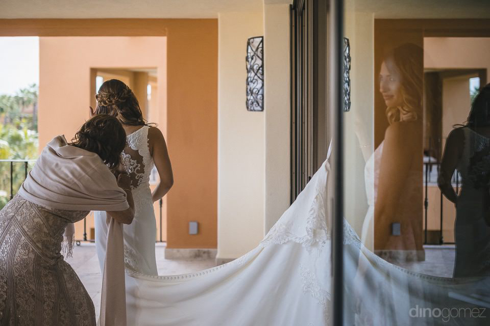 Bride putting her dress on the balcony with her mom - Chiara & Jeremee