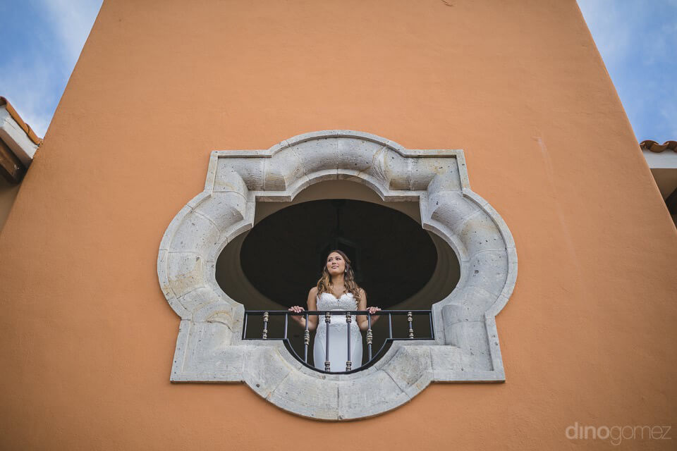 Bride looking out the window from below - Chiara & Jeremee