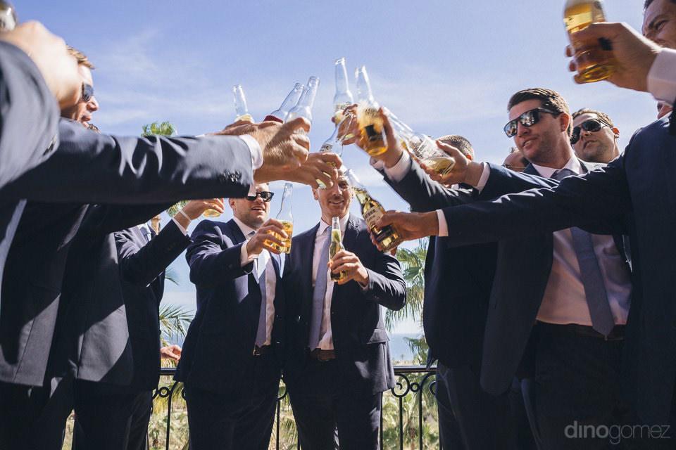 Groom and groomsmen toast with coronas - Megan & Andrew's Wedding
