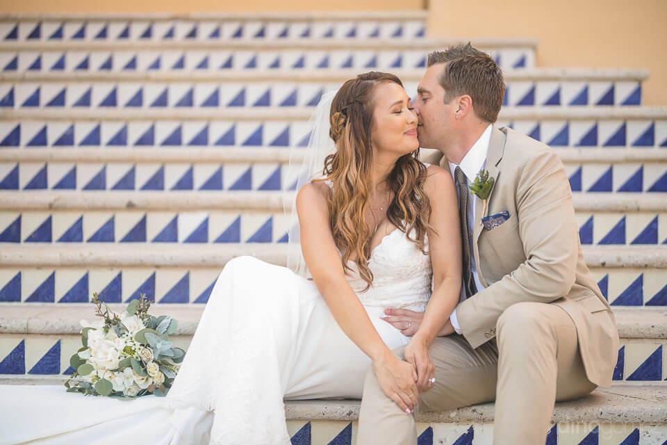 Bride and groom kissing sitting on the stairs - Chiara & Jeremee