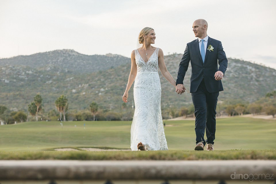 Newlyweds Walking On The Grass - Megan & Andrew'S Wedding