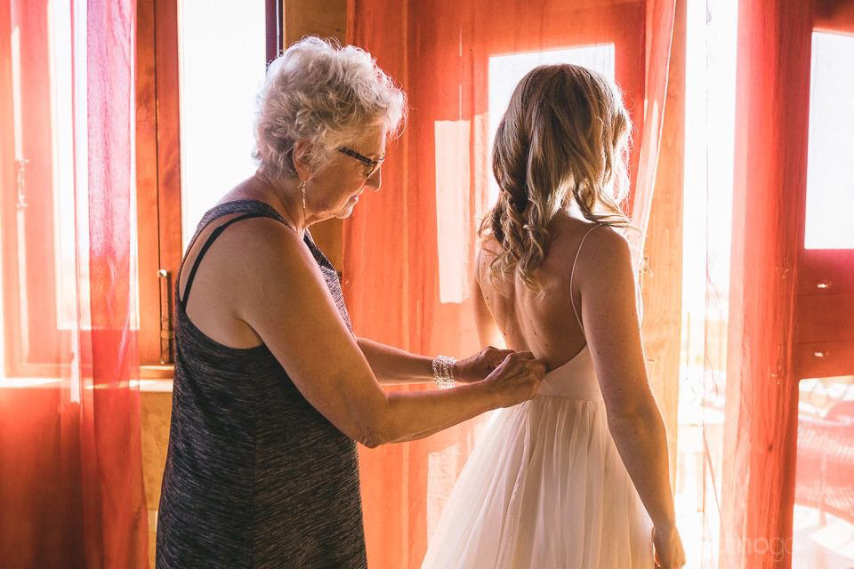Mother of the bride helping with the dress - Rachel & Destin