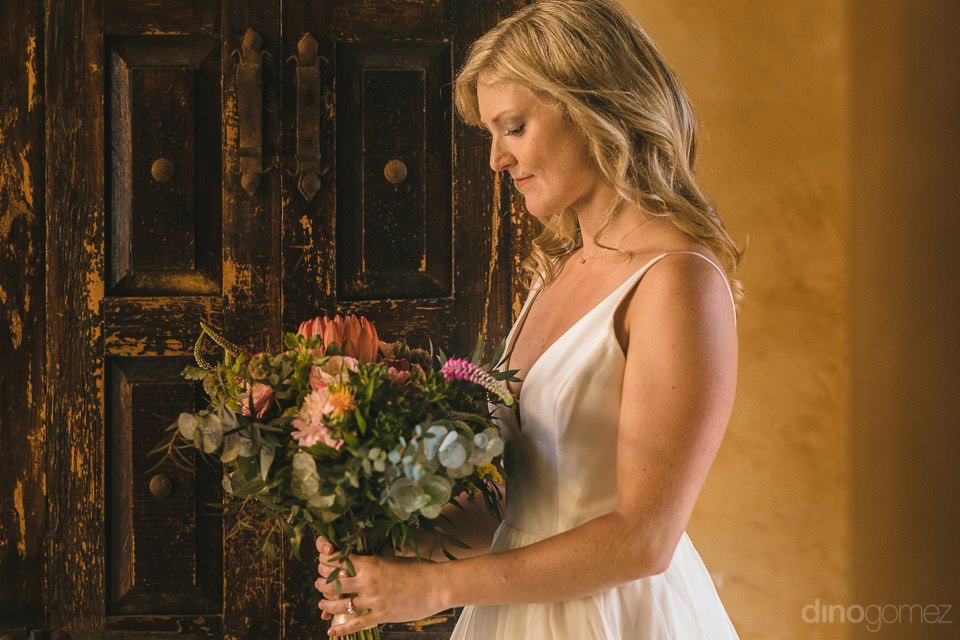 The bride looking at her flowers - Rachel & Destin