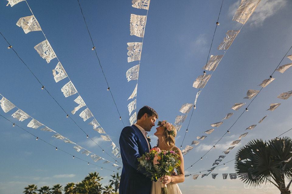 newlyweds kissing under the papel picado decor - Rachel & Destin