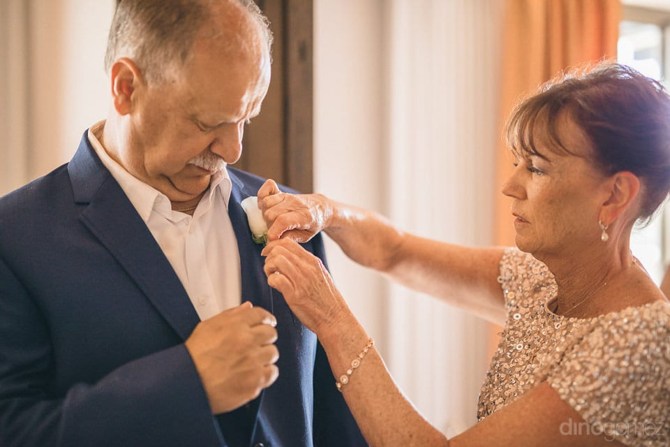 A gentleman is getting rose flower attached to the collar of the coat with full attention with the help of a lovely lady - Shannon & Jordan