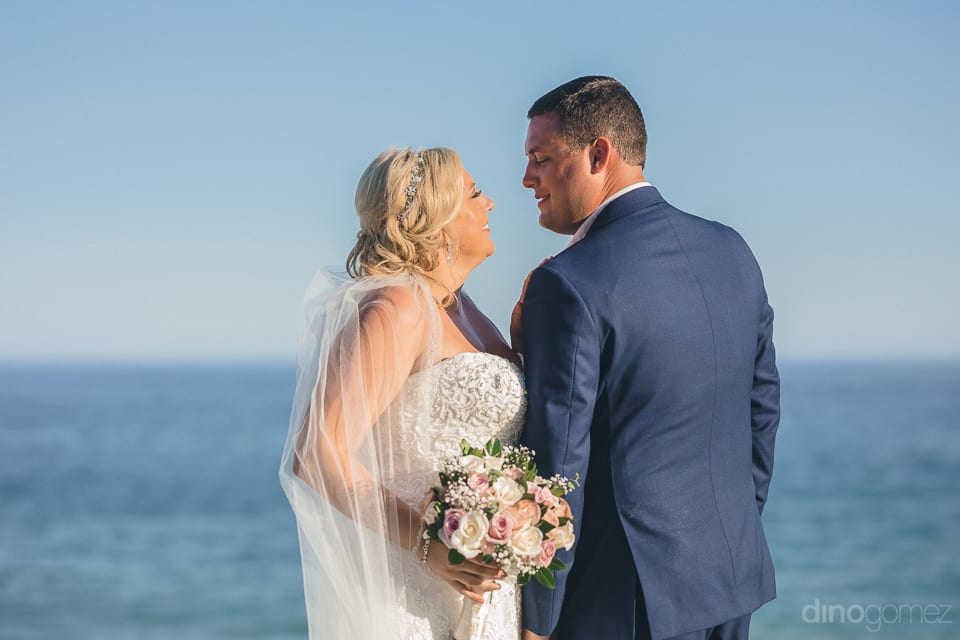 Looking elegant in white gown and handsome in blue suit, the couple is giving a romantic pose for the camera near the sea after their wedding - Shannon & Jordon