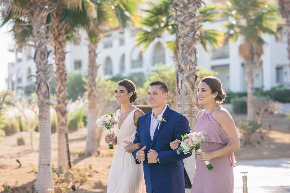 A handsome young man holding hands of two charming ladies is moving towards the wedding venue of the lovely couple - Shannon & Jordan