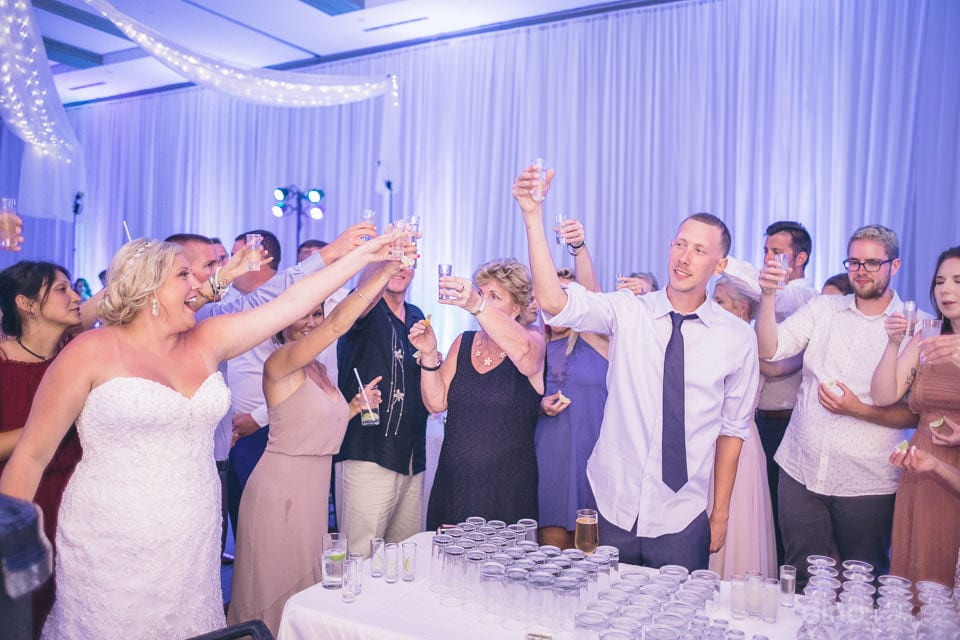 All the guests are standing together and raising a toast to the newly married couple along with the bride and groom - Shannon & Jordan