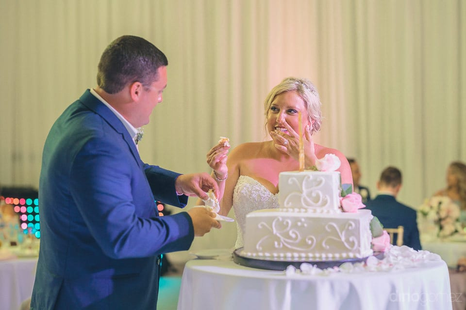 The lovely couple is smiling at each other while holding the pieces of wedding cake to share with each other - Shannon & Jordan