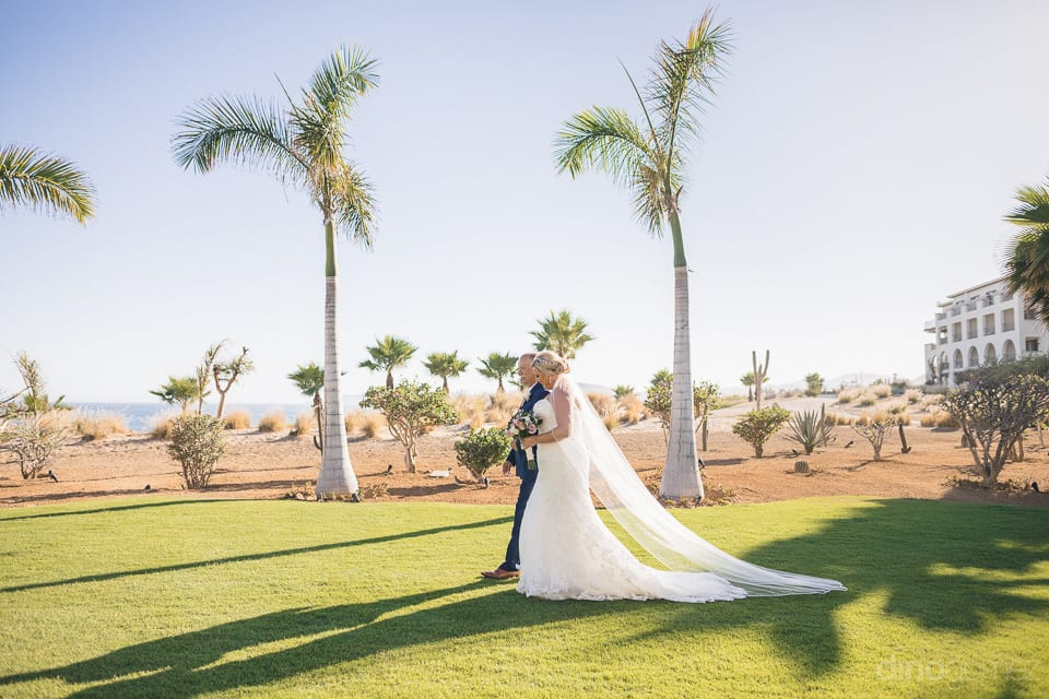 Bride is looking elegant in white wedding gown and is walking holding arms of a gentleman towards her wedding stage - Shannon & Jordan