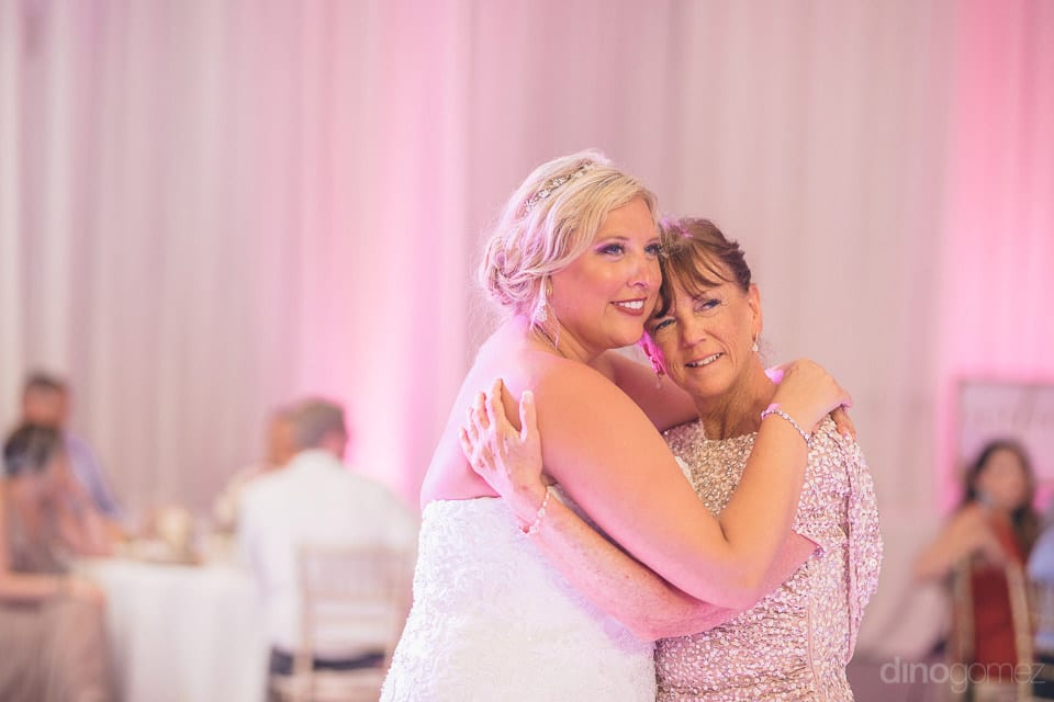 Lovely bride is hugging a beautiful lady during the evening party and both are looking at something pleasant - Shannon & Jordan
