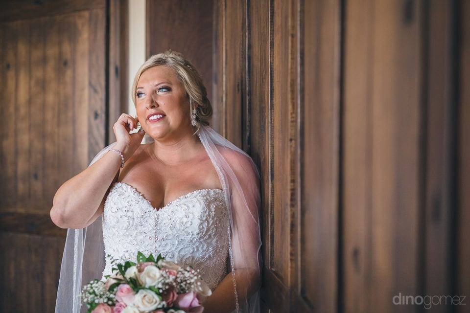 Lovely Shannon is looking wonderful in her white wedding gown with detailed lace work. She is smiling and posing beautifully for the camera - Shannon & Jordan