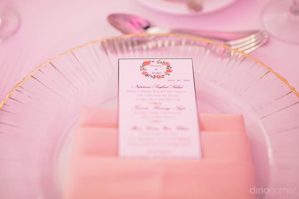 This picture captures the leaflet containing wedding information of the couple. It is beautifully placed on a light pink colored towel napkin - Shannon & Jordan