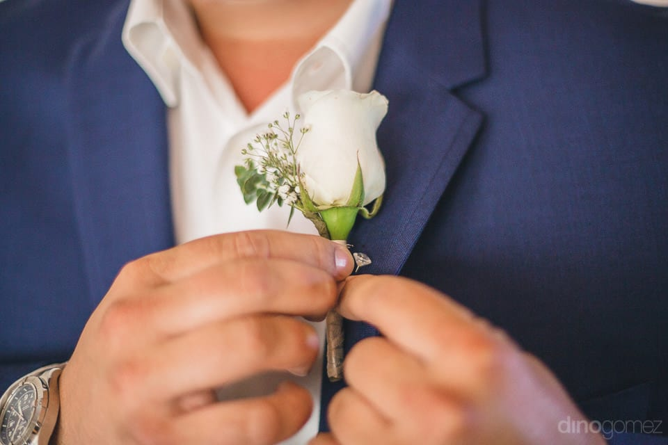 A closer view of the little white flower being tucked by the groom on the collar of his wedding coat - Shannon & Jordan