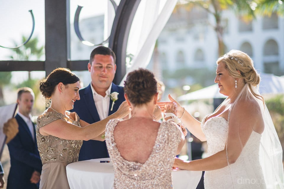 Lovely couple is standing along the side of a table and is performing a ritual with hands along with two other ladies- Shannon & Jordan