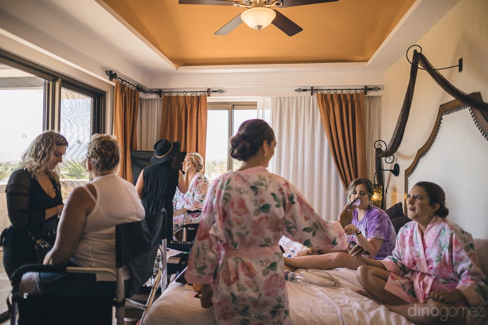 Lovely bride and her team is getting ready by the professional make-up artist inside the room before the wedding- Shannon & Jordan
