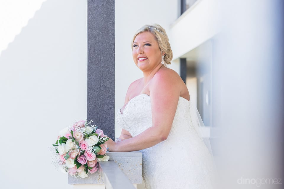 Beautiful bride in white gown is standing at a balcony of the palace to pose for the camera just before the wedding- Shannon & Jordan