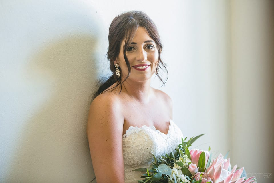 Beautiful bride smiling at the camera while holding the bouquet just befor the marriage of amazing couple- Aubrey & Chris