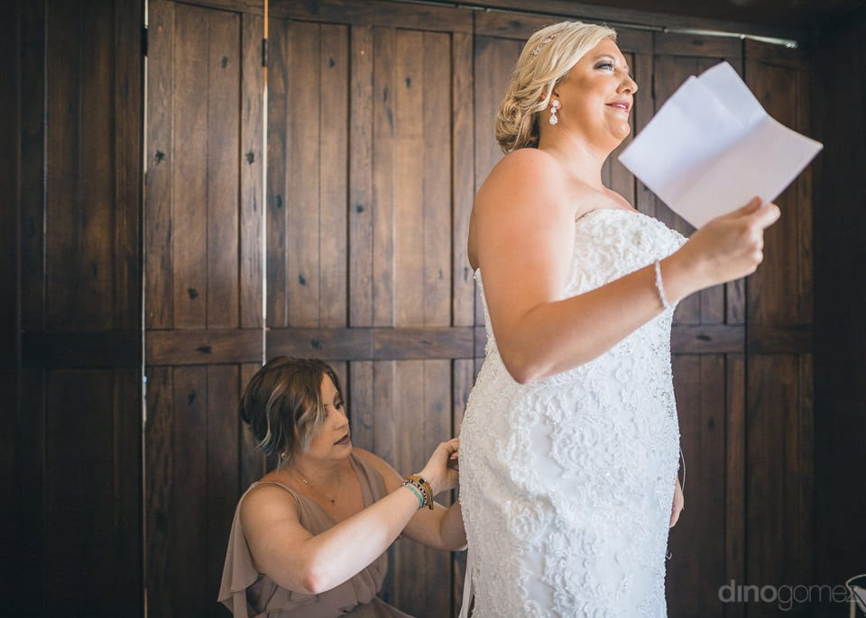 Beautiful bride is smiling brightly while her bridesmaid is setting her wedding gown-Shannon & Jordan