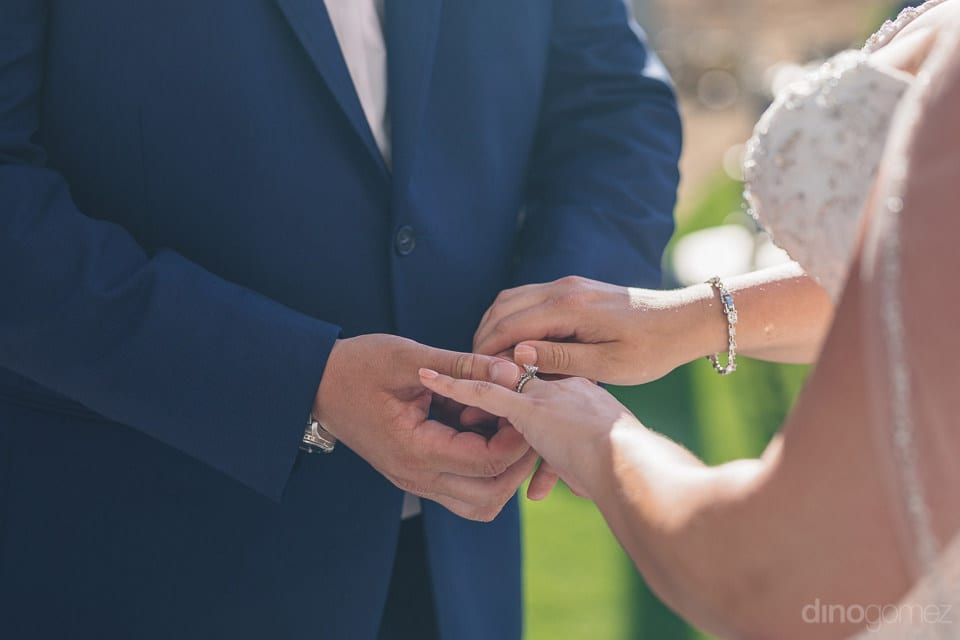 Lovely couple is holding each others hands while exchanging wedding rings during the ceremony- Shannon & Jordan