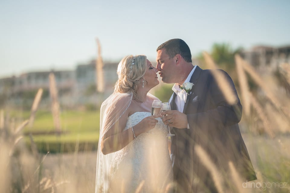 Couple is about to kiss each other with a cheers standing in beautiful golden bushes at the palace- Shannon & Jordan